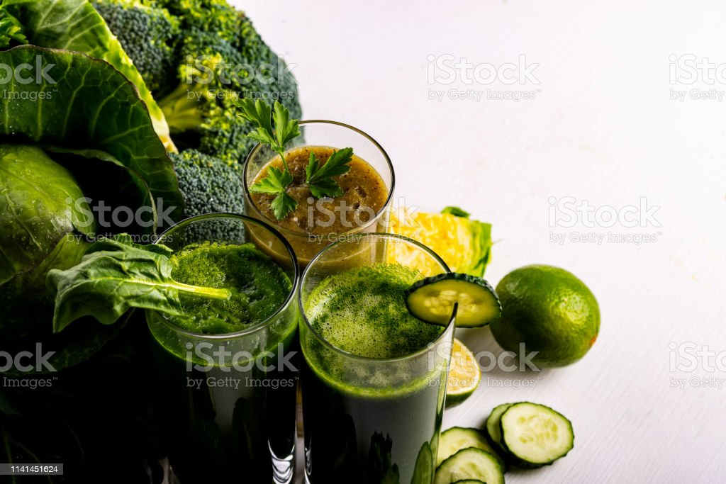 Vegan food and drinks with spinach, kiwi and cucumber on the white...