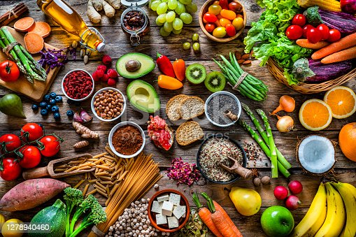 Vegan food backgrounds: large group of multicolored fresh fruits, vegetables, cereals and spices shot from above on wooden background. The composition includes green apple, kiwi, pear, pomegranate, orange, coconut, banana, grape, berries, ginger, almonds, pistachio, olive oil, olives, goji berries, chia seeds, pinto beans, nutmeg, rosemary, radish, tomatoes, carrot, kale, avocado, onion, rice, cocoa powder, sweet potato, wholegrain pasta, tofu, lettuce, corn, broccoli, pepper, asparagus, green beans, among others. High resolution 42Mp studio digital capture taken with SONY A7rII and Zeiss Batis 40mm F2.0 CF lens