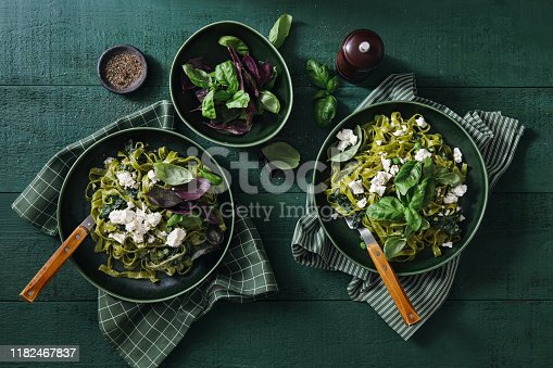 Vegan Gluten-Free Creamy Spinach Pasta and vegan cheese on dark green background