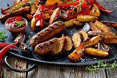 Grilled vegan sausages with hot sauce, potato wedges and vegetables
