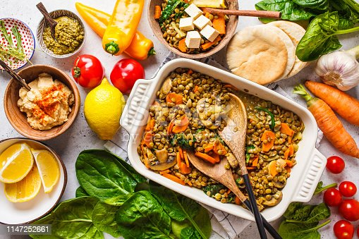 Vegan lentil curry with vegetables, top view. Healthy vegetarian food background.
