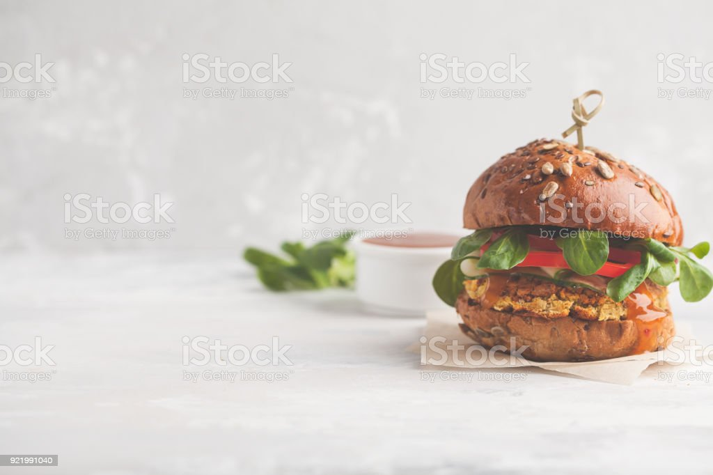 Vegan lentils burger with vegetables and curry sauce. Light background, copy space. Healthy vegan food concept. stock photo