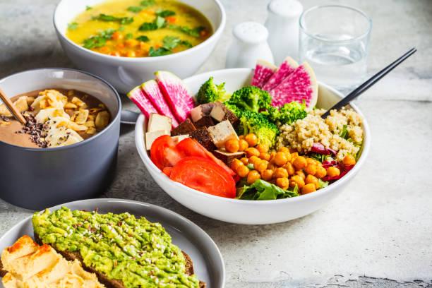 vegan lunch. chocolade smoothie bowl, buddha bowl met tofu, kikkererwten en quinoa, linzensoep en toast op een grijze achtergrond. - veganist stockfoto's en -beelden