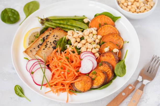veganes mittagessen, salat mit gemüse, tofu, gebackene süßkartoffel, sprossen von kichererbsen und erbsen. - englischer erbsen salat stock-fotos und bilder