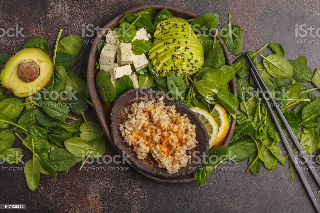 Vegan lunch with brown rice, avocado and tofu on a dark background, vegan food background, top view. stock photo