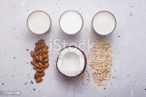 Three alternative vegan milk coconut, oat and almond in glasses next to the ingredients on a gray background. Top view, flat lay