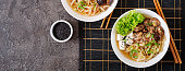 Vegan noodle soup with tofu cheese, shiitake mushrooms and lettuce in white bowl. Asian food. Top view. Banner.  Flat lay