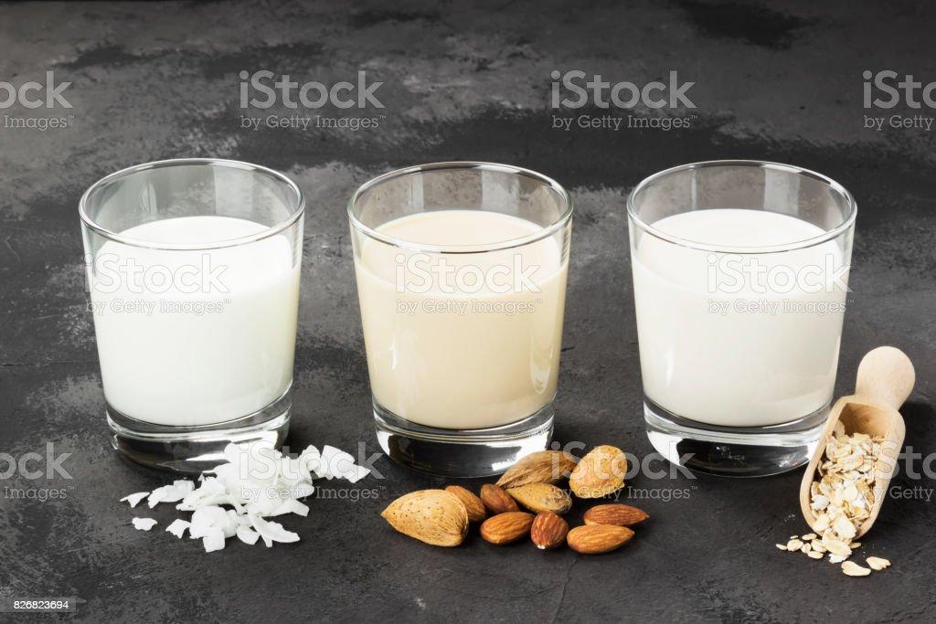 Vegan oat, almond, coconut milk in glass on a dark background....