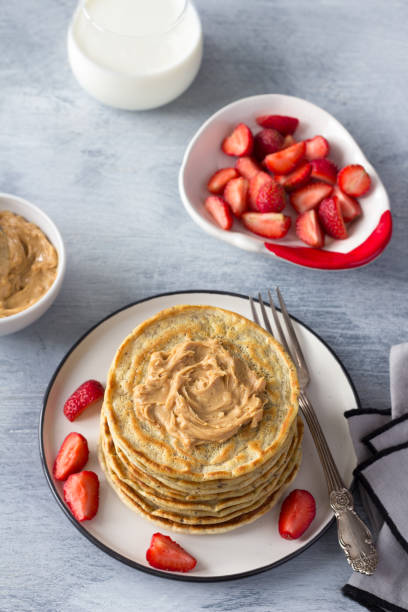 Vegane Pfannkuchen mit Leinsamen, Erdnussbutter, Erdbeere und veganer Milch auf einem weißen Teller auf grauem Hintergrund – Foto