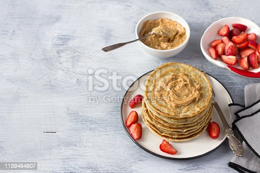 istock Vegan pancakes with flax seeds, peanut butter, strawberry and vegan milk on a white plate on a gray background 1159464607