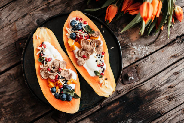 Vegan Papaya Boats – the new kind of breakfast buddha bowls stock photo