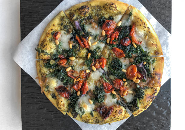 Vegan Pizza with Kale, Pesto, Peppers, Tomatoes, Onions, Plant Cheese stock photo