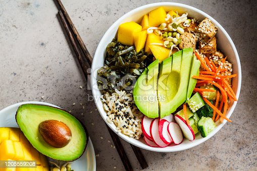 istock Vegan poke bowl with avocado, tofu, rice, seaweed, carrots and mango, top view. Vegan food concept. 1205559208