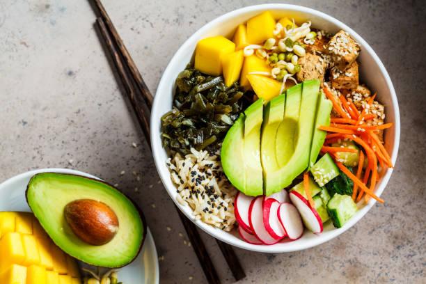tazón de poke vegano con aguacate, tofu, arroz, algas, zanahorias y mango, vista superior. concepto de comida vegana. - vegana fotografías e imágenes de stock