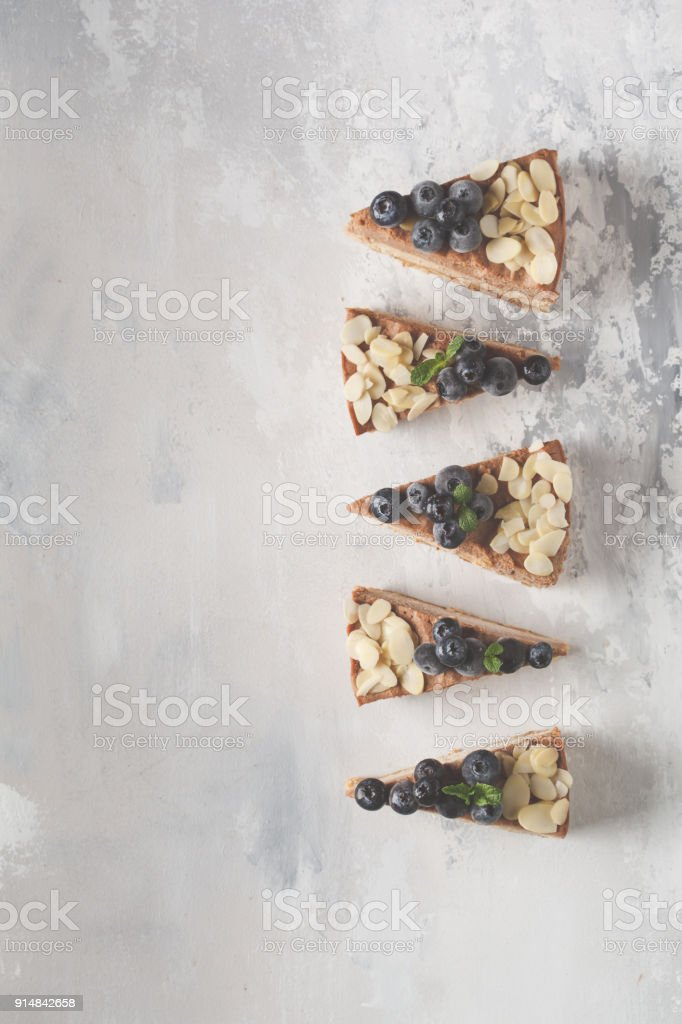 Vegan raw chocolate cheesecake with blueberries and almonds. Healthy vegan food concept, food background, copy space, top view. stock photo