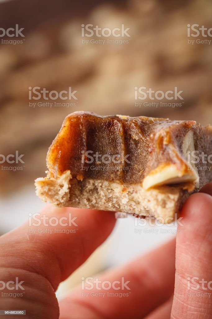 Vegan raw homemade peanut candy bar in hand. Healthy lifestyle and raw vegan food concept. royalty-free stock photo