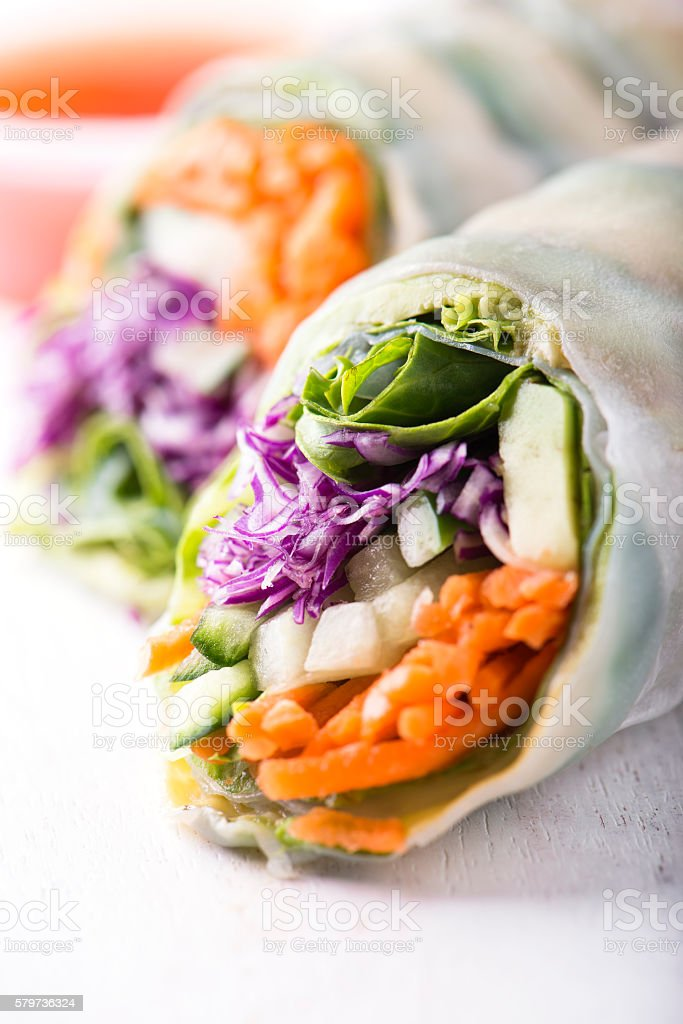 vegan rice paper spring rolls with veggies over white stock photo
