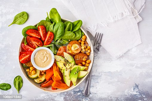 istock Vegan salad bowl with baked vegetables, chickpeas, avocado and tahini dressing on a white background, top view. 1069471340