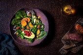 Vegan salad of raw vegetables in moody dark rusty background