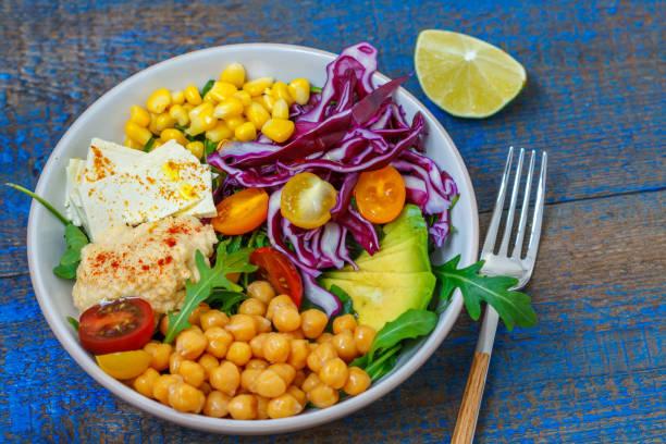 Vegan salad with hummus, tofu, chickpeas and vegetables stock photo