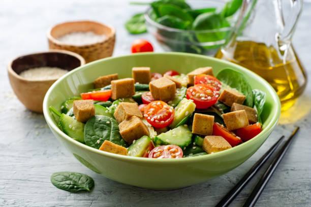 veganistische salade met spinazie, komkommer, tomaten, avocado, gebraden tofu en sesam - vleesvervanger stockfoto's en -beelden