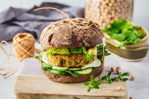 Vegan sandwich with chickpea patty, avocado, cucumber and greens in rye bread.