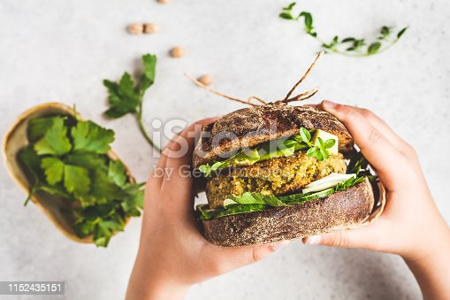 Vegan sandwich with chickpea patty, avocado, cucumber and greens in rye bread in children's hands, top view.