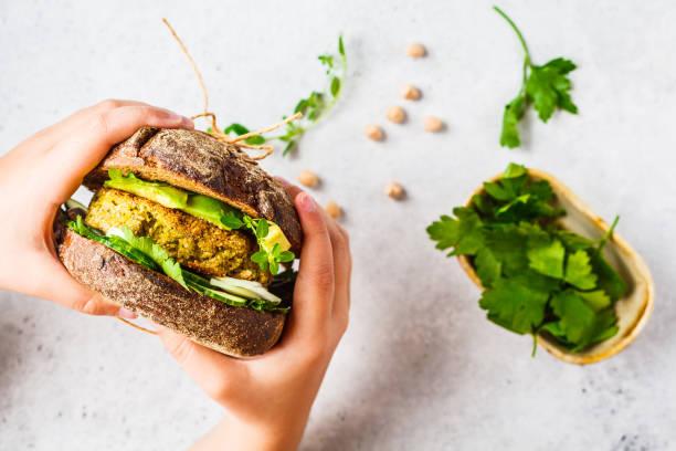 sándwich vegano con hamburguesa de garbanzos, aguacate, pepino y verduras en pan de centeno en las manos de los niños. - vegana fotografías e imágenes de stock