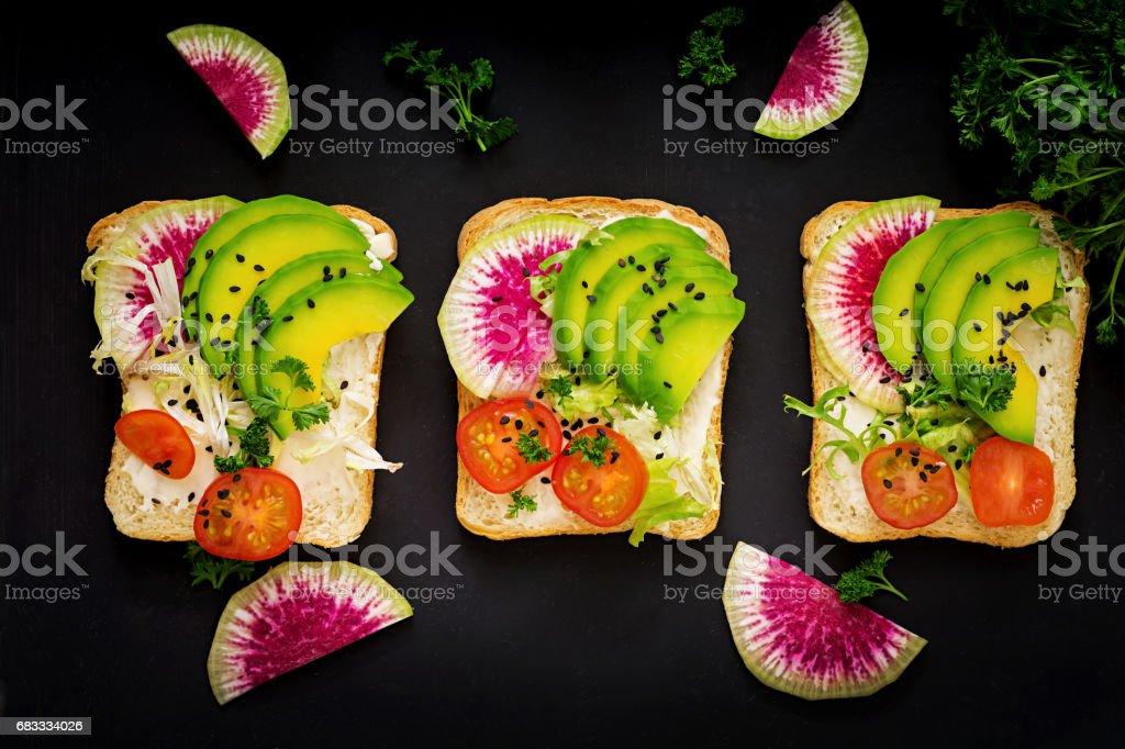 Sandwichs de végétalien avec avocat, radis pastèque et tomates sur un fond noir. Poser de plat. Vue de dessus photo libre de droits