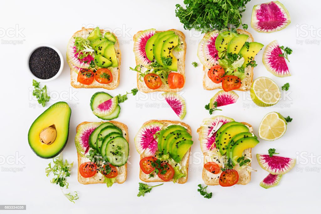 Vegan sandwiches with avocado, watermelon radish and tomatoes on a white background. Flat lay. Top view royalty-free stock photo