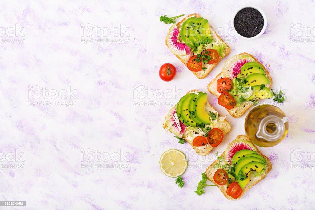 Sandwichs de végétalien avec avocat, radis pastèque et tomates sur un fond blanc. Poser de plat. Vue de dessus photo libre de droits