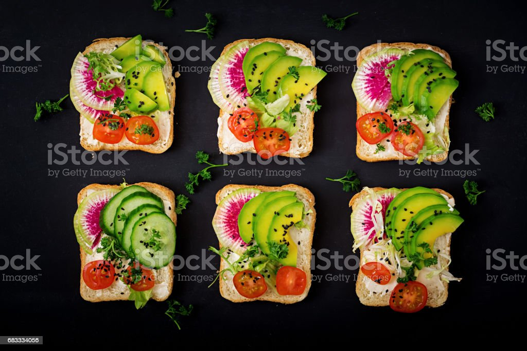 Vegan sandwiches with avocado, watermelon radish and tomatoes on a black background. Flat lay. Top view royalty-free stock photo