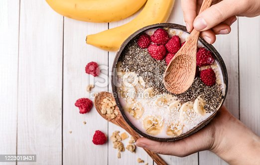 istock Vegan smoothie bowl with chia pudding, berries and granola in a coconut shell on a white wooden background. Plant based diet concept.hand holds a spoon in the frame 1223019431