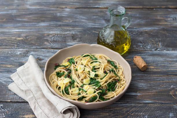 Vegane Spaghetti mit Mangold und Knoblauch auf einem Holztisch – Foto