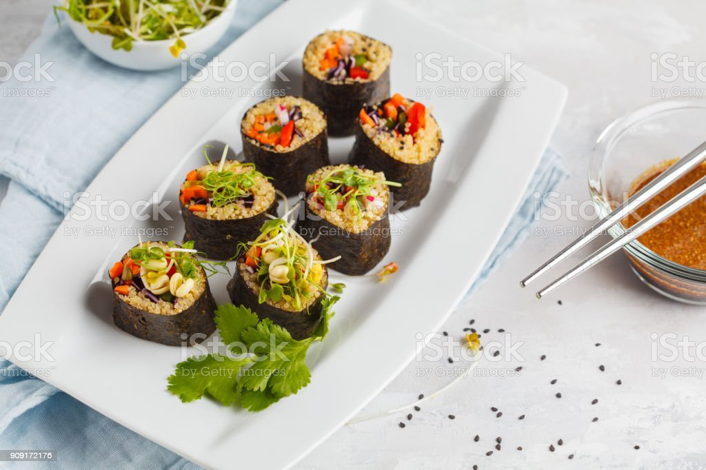 Vegan sushi rolls with quinoa, vegetables and soy-nut sauce on a white plate, light background. Vegan Healthy Food Concept. stock photo