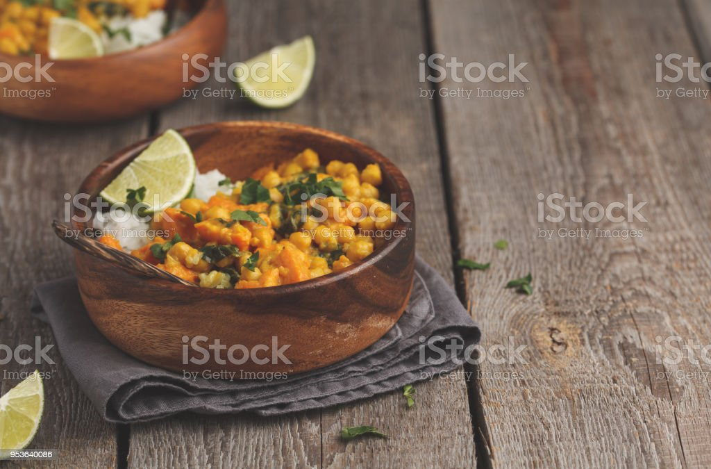 Vegan Sweet Potato Chickpea curry in wooden bowl on a wooden background. Healthy vegetarian food concept. stock photo