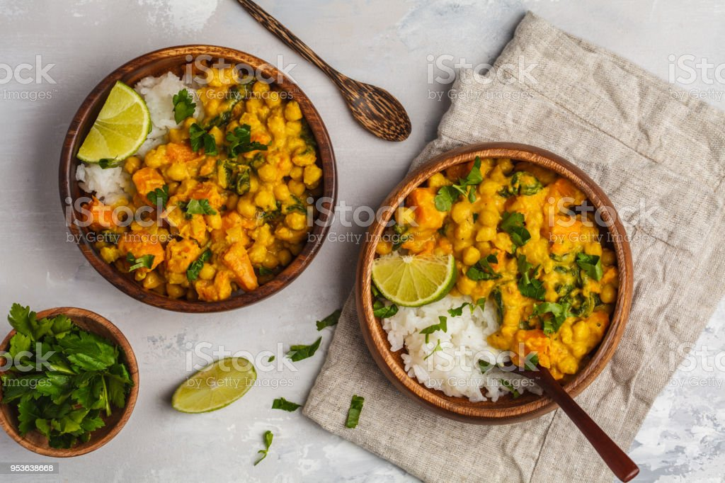 Vegan Sweet Potato Chickpea curry in wooden bowl on light background, top view, copy space. Healthy vegetarian food concept. stock photo