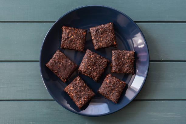 vegane süßigkeiten. leckere mandel brownies auf marineblau teller auf türkis hintergrund exemplar - marinekuchen stock-fotos und bilder