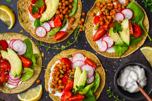 vegan tacos with baked chickpeas, avocado, sauce and vegetables on dark background, top view. - vegetariano foto e immagini stock