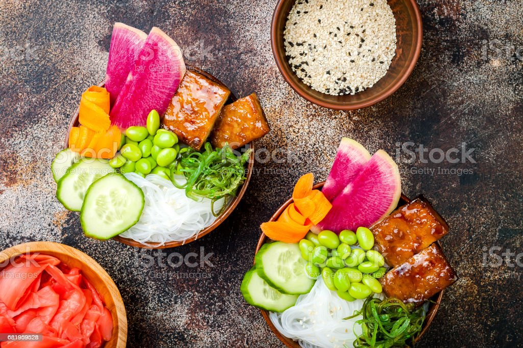Vegan tofu poke bowls with seaweed, watermelon radish, cucumber, edamame beans and rice noodles. Copy space stock photo