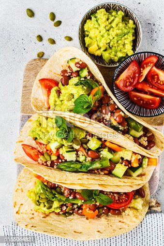Vegan tortilla wraps with quinoa, asparagus, beans, vegetables and guacamole.