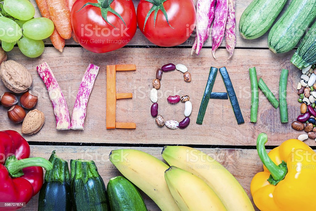 vegan word on wood background and vegetable stock photo