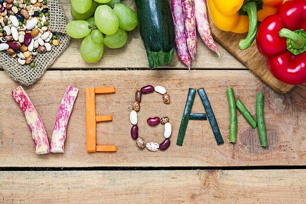 palabra vegana sobre fondo de madera y verdura - vegana fotografías e imágenes de stock