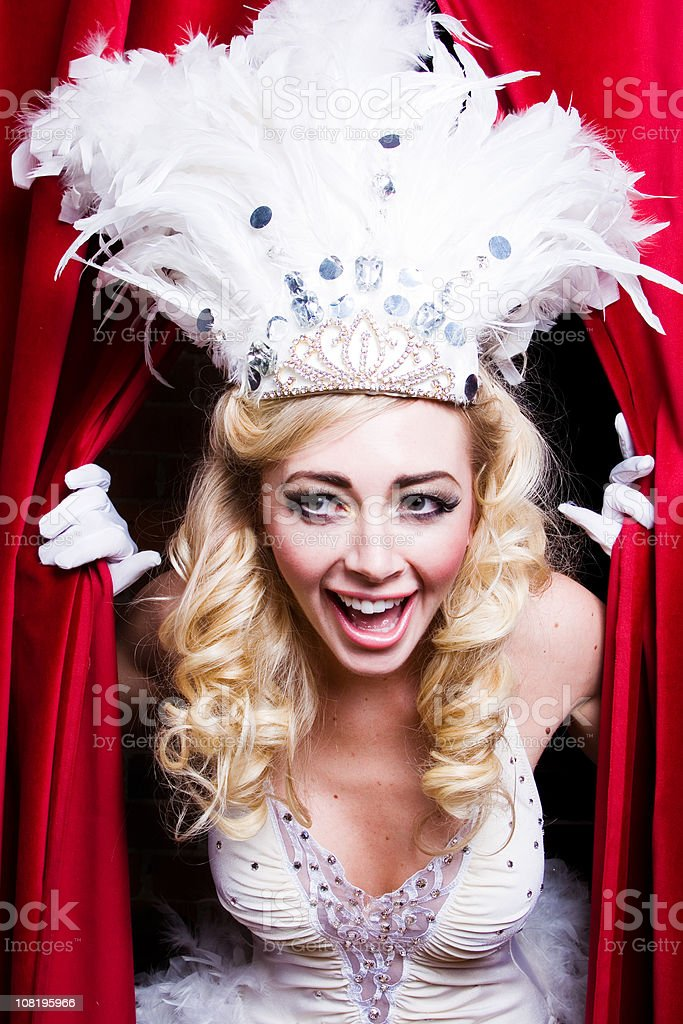 Vegas Showgirl in Costume Peeking Through Red Curtains royalty-free stock photo