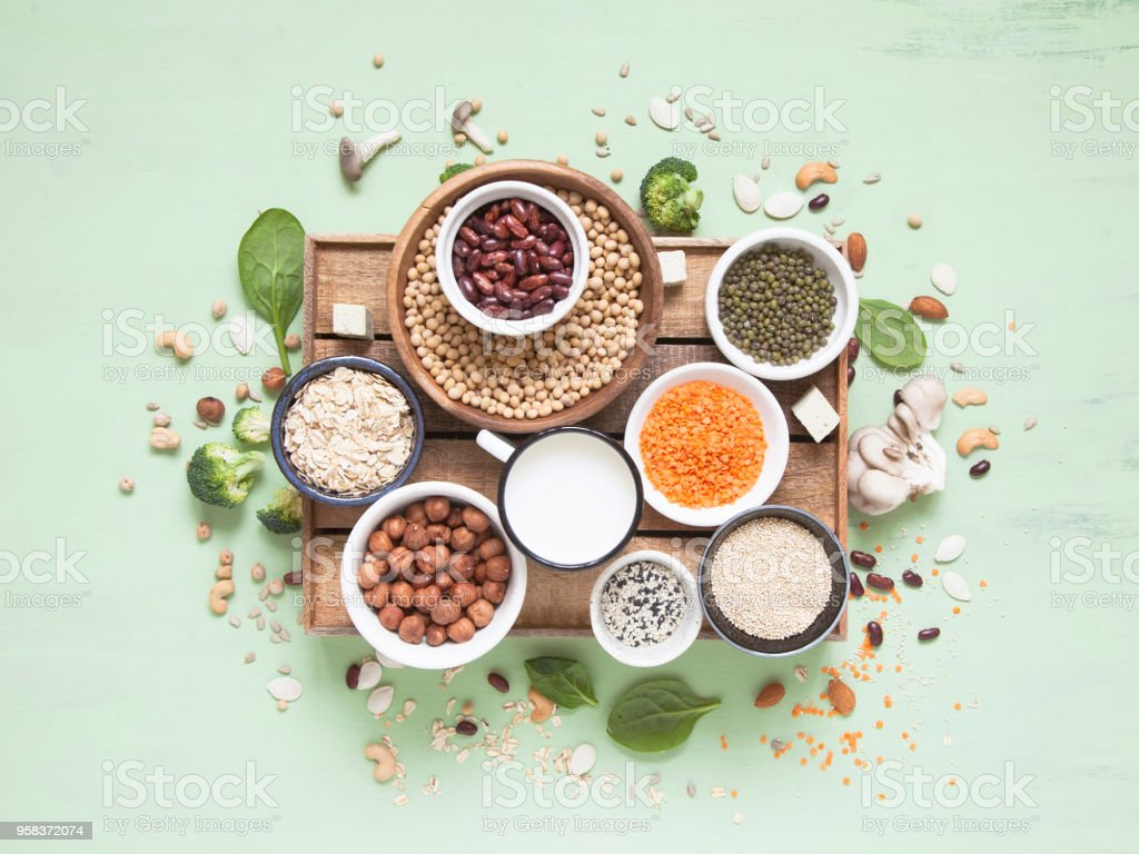 Vegetable albumen sources. Plant protein (beans, nuts, vegetables, mushrooms, seeds) on green background. stock photo