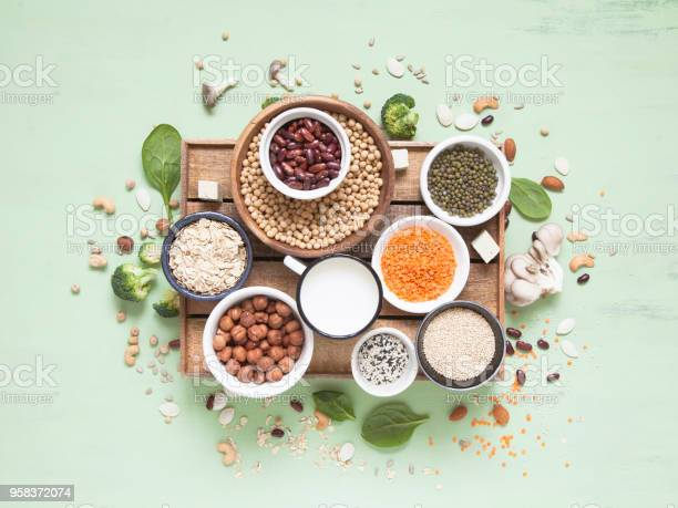 Vegetable albumen sources. Plant protein (beans, nuts, vegetables, mushrooms, seeds) on green background. Vegan and vegetarian food concept. Flat lay.