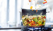 Vegetable broth in a half of saucepan. Food concept. Flying vegetables. Steel and hot saucepan. Cooking. Dish on the plate. More vegetables. Good food. The boiling tasty meal