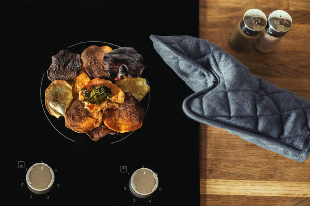 gemüse chips liegen auf einem e-herd und kochen. - gemüsechips stock-fotos und bilder