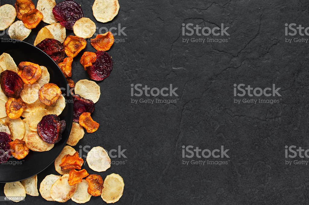 Vegetable chips on the black plate stock photo