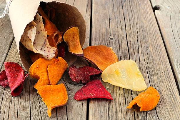 vegetable chips spilling from a paper cone on rustic wood - gemüsechips stock-fotos und bilder